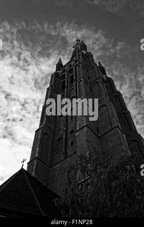 tall church spire with dark threatening clouds in black and white - Stock Photo