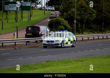 A Police Scotland police car escorting a Forth Ports Crane on the Kingsway West Dual Carriageway in Dundee, UK - Stock Photo
