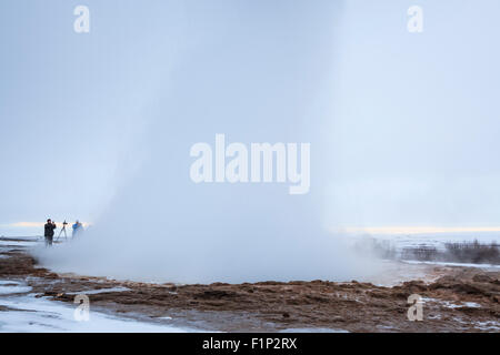 Visitors watching the famous Strokkur geyser wich erupts about every 4–8 minutes. Geysir. Haukadalur. Iceland. - Stock Photo