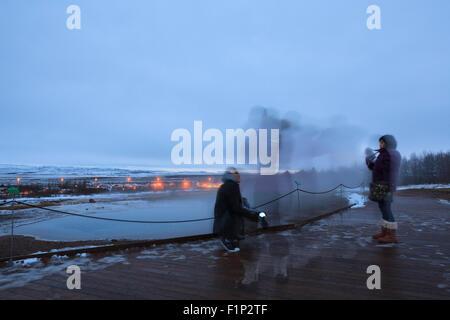 Visitors watching the geothermal pools close to Strokkur geyser. Geysir. Haukadalur. Iceland. - Stock Photo