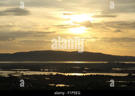 The Irrawaddy River (Ayeyarwady River) flows past Mandalay, Myanmar. The evening sun reflects on the water. - Stock Photo