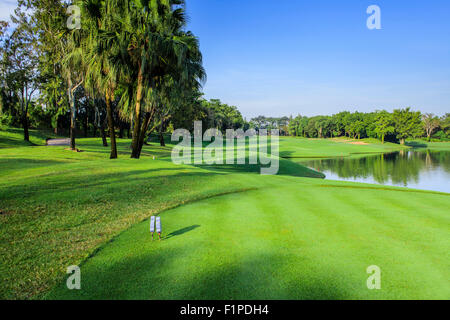 Beautiful green golf course in a sunny day, Thailand - Stock Photo