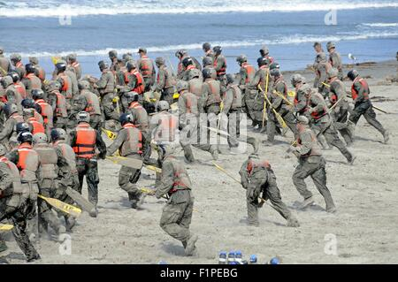 US Navy SEAL candidates cover themselves in sand during surf passage on Naval Amphibious Base Coronado September - Stock Photo