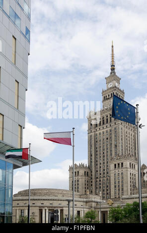 Palace of Culture - Palac Kultury architecture with 3 flags Polish, European Union and United Arab Emirates in Warsaw, - Stock Photo