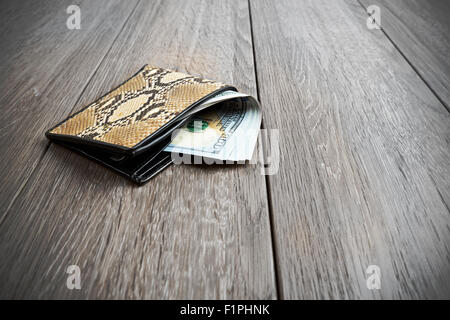 snake leather wallet with money on wooden background - Stock Photo
