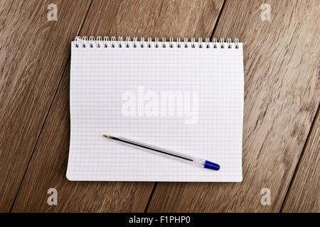 Notebook and pen. Blank white page over wooden  background - Stock Photo