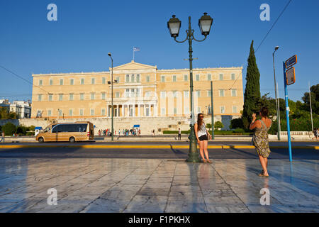 Tourists taking photos in front of the building of Greek parliament - Stock Photo