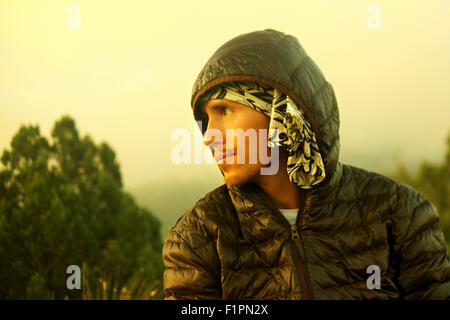 Young handsome man with beard in autumn dark jacket hooded down in the wild looks away. Filter was used. - Stock Photo