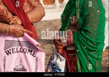 Amritsar, Punjab, India. Two women, their hands painted with intricate henna designs. One holds a pink plastic bag - Stock Photo