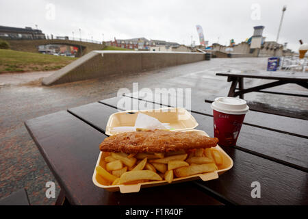 deep fried cheap fish and chips on a wet summers day at a seaside resort in north wales uk - Stock Photo