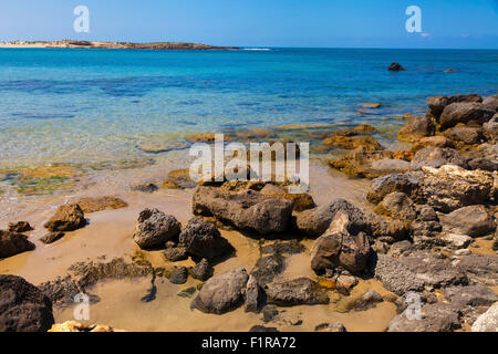 Water edge with large rocks on the sand and view of calm sea waters - Stock Photo