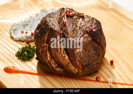 Large grilled steak served with condiments on a wooden plate. Healthy dinner - Stock Photo