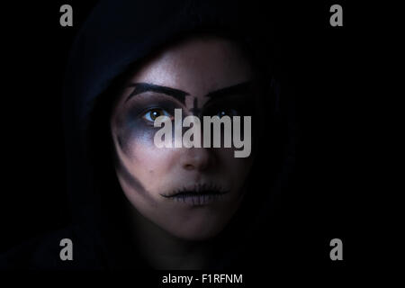 Teen girl wearing hood with scary face makeup on black background. - Stock Photo