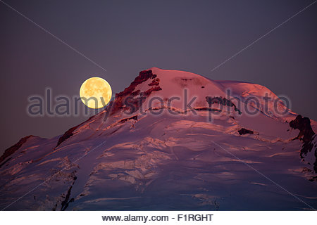 The full moon sets behind Mount Baker as the light of sunrise turns the peak of the volcano's cone red. - Stock Photo