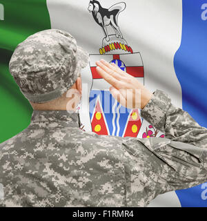 Soldier saluting to Canadial province flag conceptual series - Yukon - Stock Photo