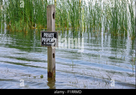 Private property sign on wooden post in wetlands. - Stock Photo