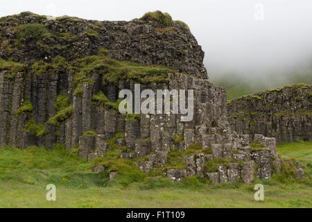 A belt of basalt columns at Dverghamrar with cliffs behind rising into the mist - Stock Photo