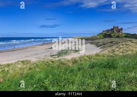 Bamburgh Castle across the dunes, early summer afternoon, Northumberland, England, United Kingdom, Europe - Stock Photo