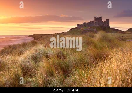 Sunrise over the dunes at Bamburgh Castle in Northumberland, England. - Stock Photo
