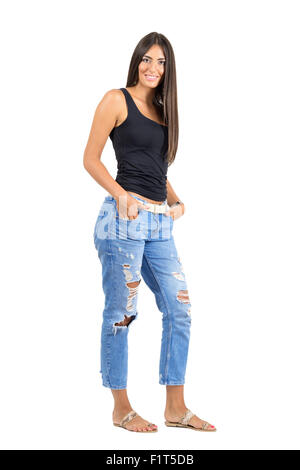 Young happy tanned woman with hands in pocket smiling at camera. Full body length portrait isolated over white studio - Stock Photo