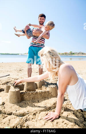 Parents and son making sandcastle on beach - Stock Photo