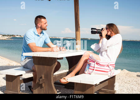 Young woman at beach bar taking photos of friend - Stock Photo