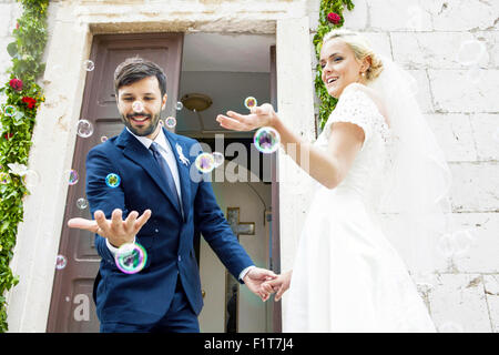 Bride and groom playing with soap bubbles in front of chapel - Stock Photo