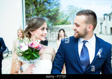Bride and groom walking with wedding guests in background - Stock Photo