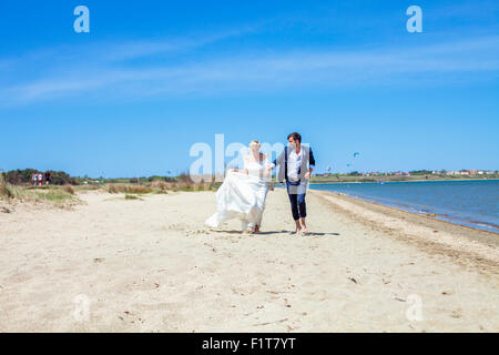 Bride and bridegroom running on beach - Stock Photo