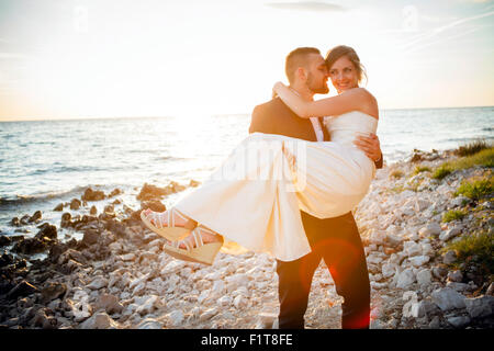 Groom carrying bride on pebble beach at sunset - Stock Photo