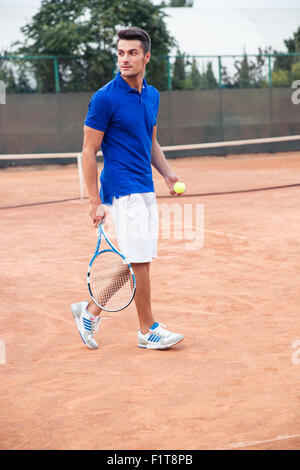 Full length portrait of a handsome man playing in tennis outdoors - Stock Photo