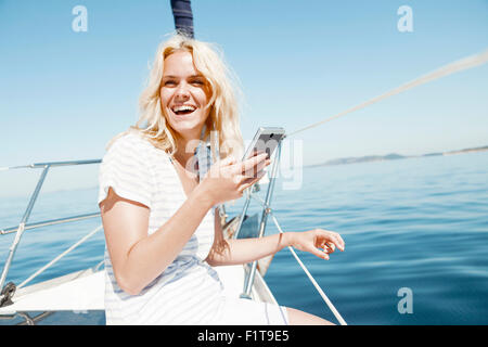 Young woman using smart phone on sailboat, Adriatic Sea - Stock Photo