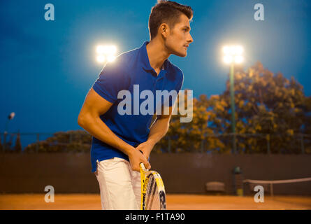 Portrait of a handsome man playing in tennis outdoors at the night - Stock Photo