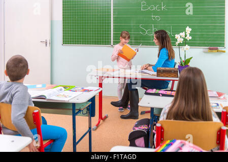 Students read a woman teacher at the blackboard - Stock Photo