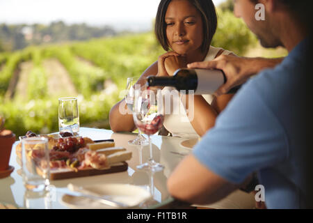 Young woman sitting at a table while man pouring some red wine into his glass. Couple at winery restaurant drinking red wine. Stock Photo