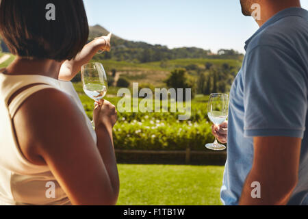 Young couple on vacation holding a glass of wine, with woman pointing away at vineyard, showing something to her - Stock Photo