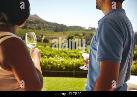 Couple standing together holding glasses of white wine with vineyard in background. Man and woman standing outdoors - Stock Photo
