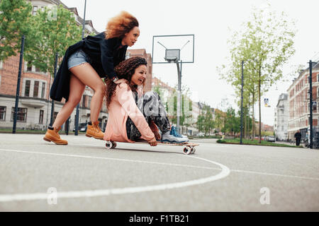 Woman pushing her friend on skateboard. Young women having fun together outdoors. - Stock Photo