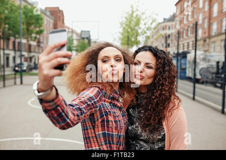 Happy young girls pout and pose for a selfie. Young girl friends taking a self portrait using mobile phone, outdoors - Stock Photo
