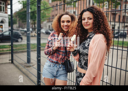 Portrait of beautiful young women standing against a fence looking at camera while eating ice cream. - Stock Photo