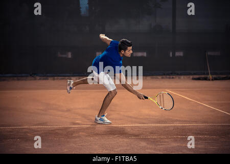 Portrait of a man playing in tennis - Stock Photo