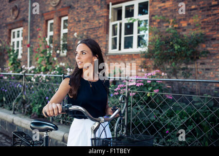 Outdoor shot of young woman walking along the road with a bicycle looking away. Woman with bike walking down the - Stock Photo