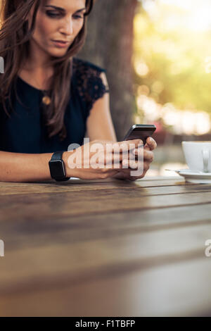 Cropped image of young female reading a text message on her smart phone. Woman using smart phone in a outdoor cafe. - Stock Photo