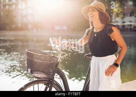 Portrait of beautiful young woman wearing a hat with a bicycle walking along a pond. Happy woman with a bike at - Stock Photo