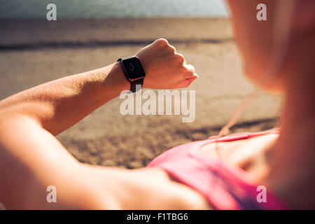 Closeup shot of young female jogger ready to run set and looking at sports smartwatch. Fitness woman checking her - Stock Photo