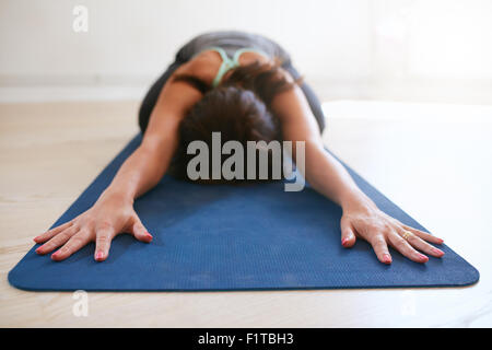 Woman doing stretching exercise on yoga mat. Fitness female performing yoga on exercise mat at gym. Child Pose, - Stock Photo