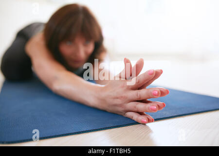 Woman doing stretching workout on fitness mat with her hands clasped. Fit female doing yoga on exercise mat at gym. - Stock Photo