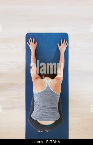 Top view of woman curls up and stretches forward, performing a yoga. Fitness female on exercise mat over light hardwood - Stock Photo