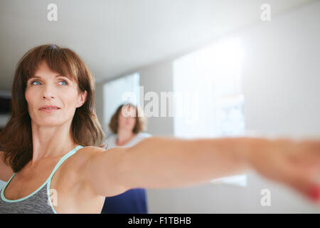 Confident female trainer doing yoga workout at gym. Women practicing yoga at class. - Stock Photo