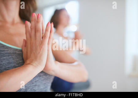 Close up shot of women at yoga class meditating with hands clasped. Female hands in namaste gesture during yoga - Stock Photo